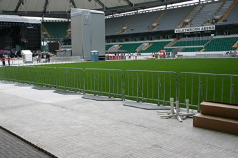 A row of vertical police barriers are installed surrounding at the football ground.