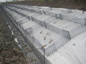 Mounted hexagonal double twisted gabion mattresses are fastened together before rock filling.