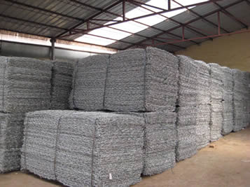 Several woven gabion baskets are packed in bundles and placed in the storehouse.